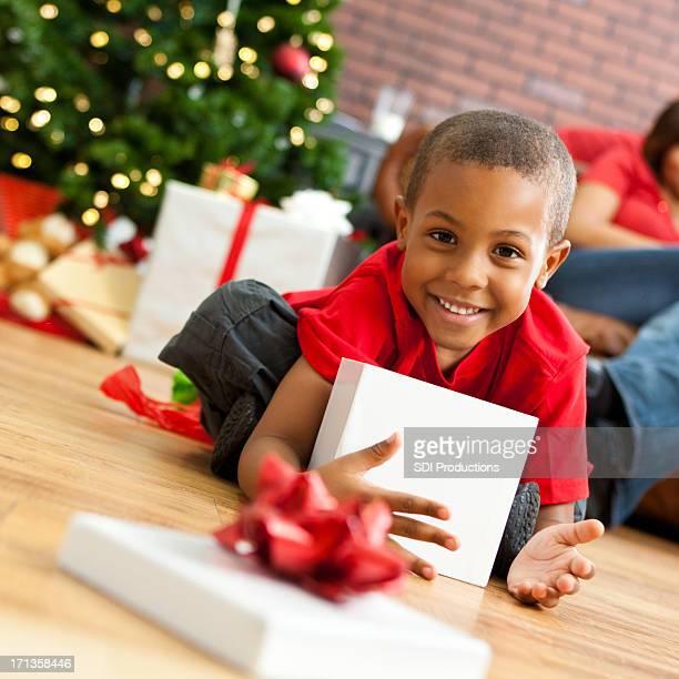 Little boy opening present on Christmas morning