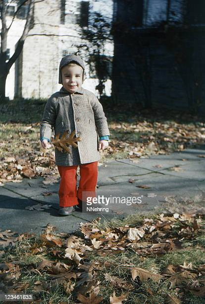 little boy outdoors in coat and hat autumn 1955, retro