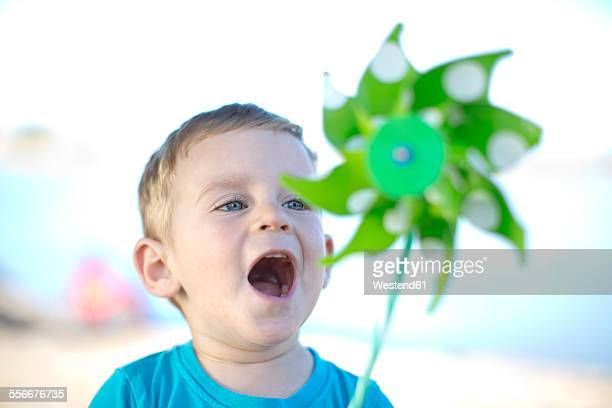 Little boy outdoors playing with paper windmill