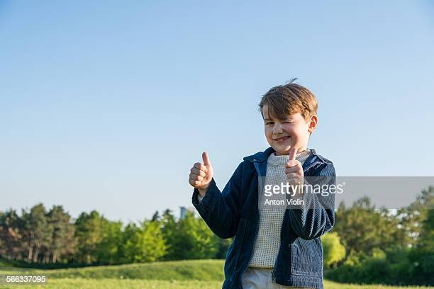 Little boy outdoors showing thumbs-up