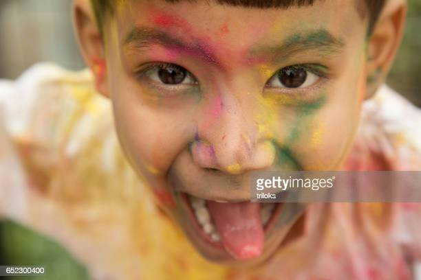 Little boy painted his face with multi colors