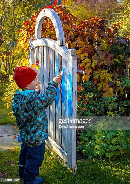 Little boy painting a garden gate blue