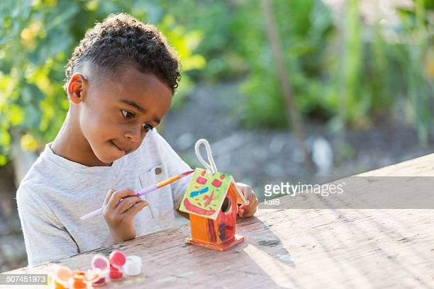 Little boy painting bird house