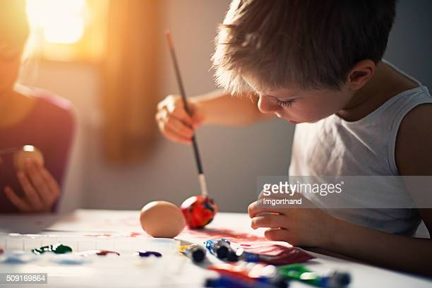 Little boy painting easter eggs