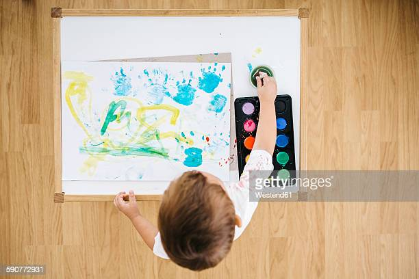 Little boy painting with watercolours