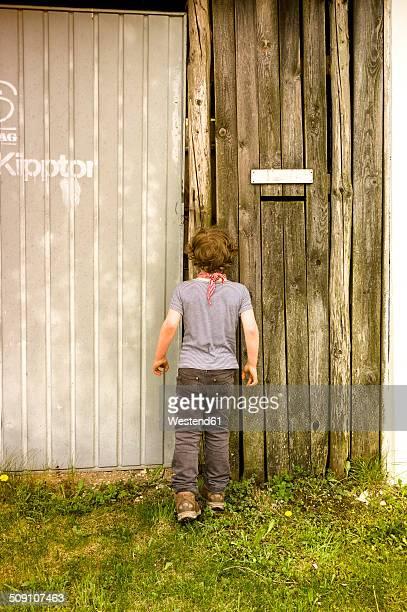 Little boy peeking through spy hole in garage