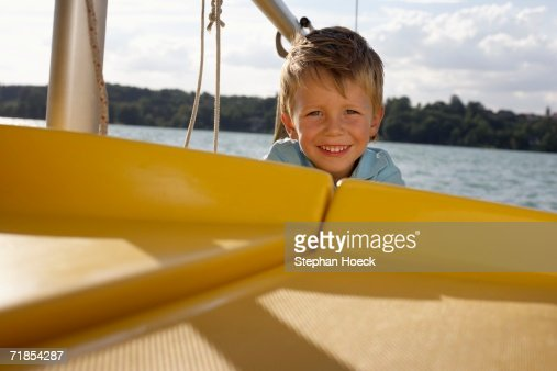 Little boy peering over the edge of a plastic boat : Stock Photo