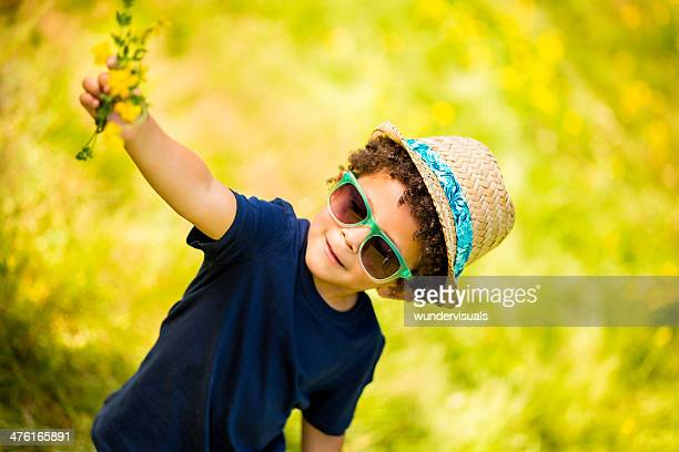 Little boy picking flowers in nature