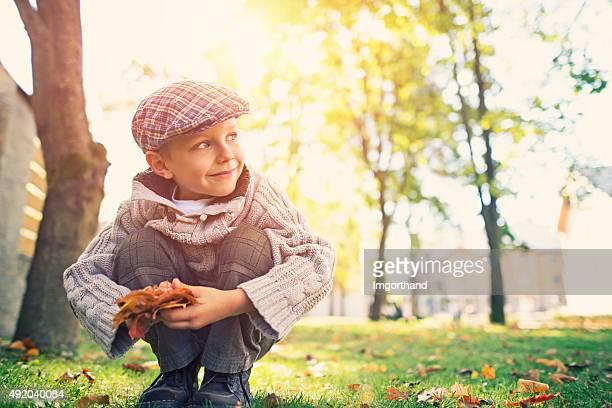 Kleine Junge heben Blätter im Herbst park