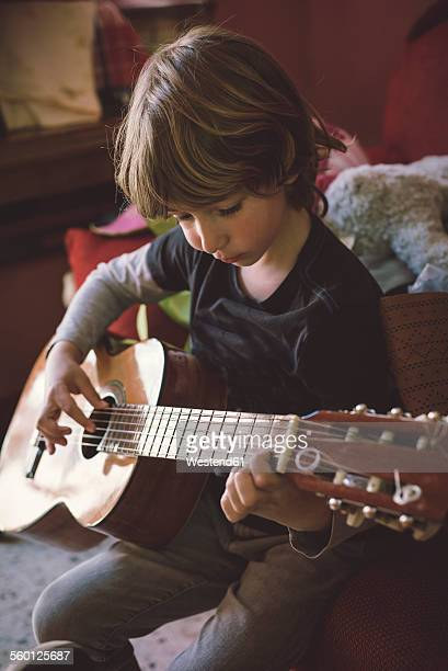 Little boy playing acoustic guitar at home