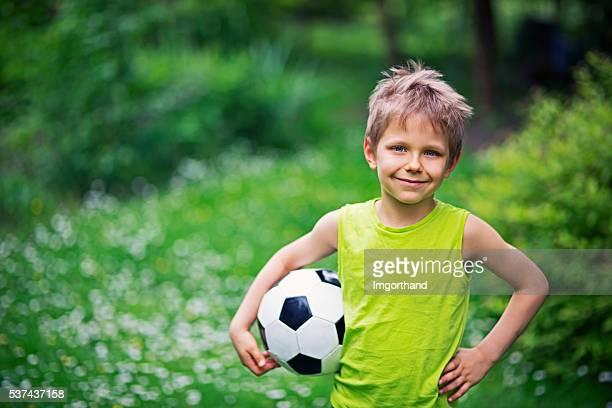 Wenig Junge spielt Fußball im Garten