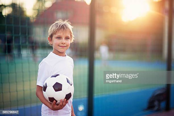 Little boy playing football in the schoolyard