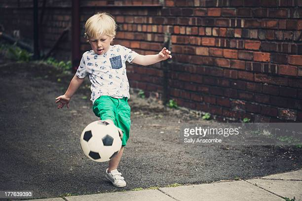 Little boy playing football