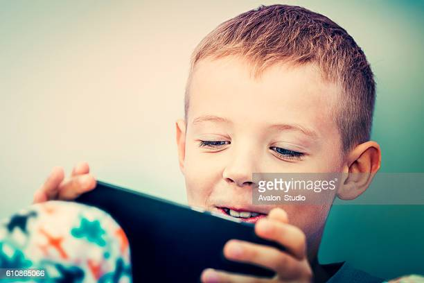 Little boy playing games on mobile phone