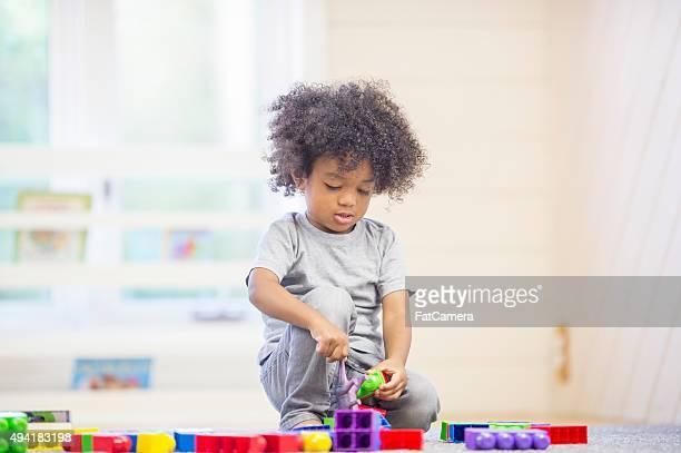 Fröhlich kleiner Junge spielt mit Spielzeug