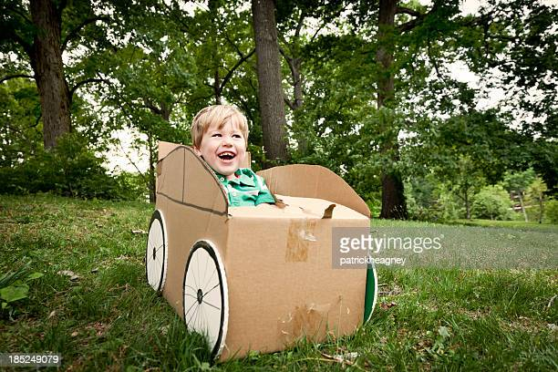 A little boy playing in a cardboard car outside