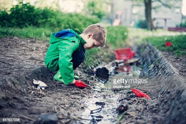 Kleiner Junge spielt in einem schmutzigen Abfluss Graben voller Müll