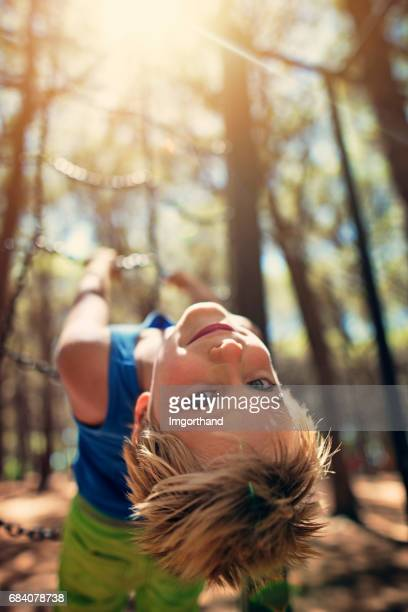 Little boy playing in pine forest playground