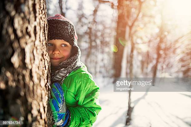 Little boy playing in sunny winter forest