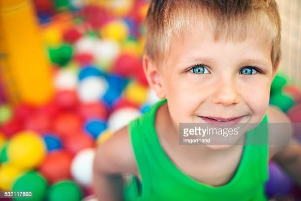 Little boy playing in the ball pool