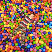 Baby boy spending time in the pool filled with balls. Indoor activities. Leisure time for children. Kid plays with colorful plastic balls at entertainment center. Laughter therapy background.