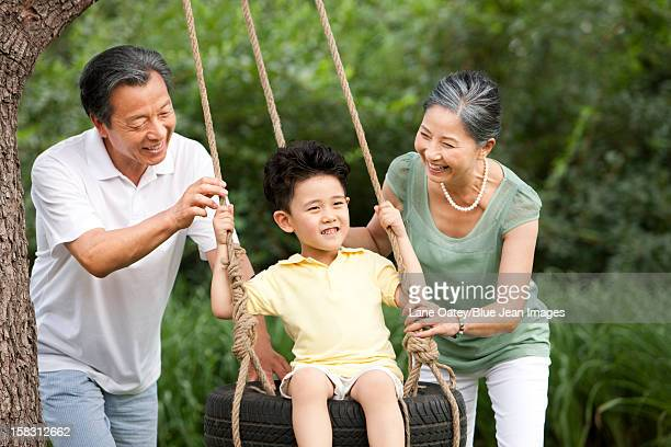 Little boy playing on a swing with grandparents beside