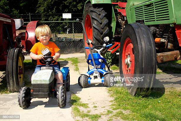 Little boy playing on a toy tractor