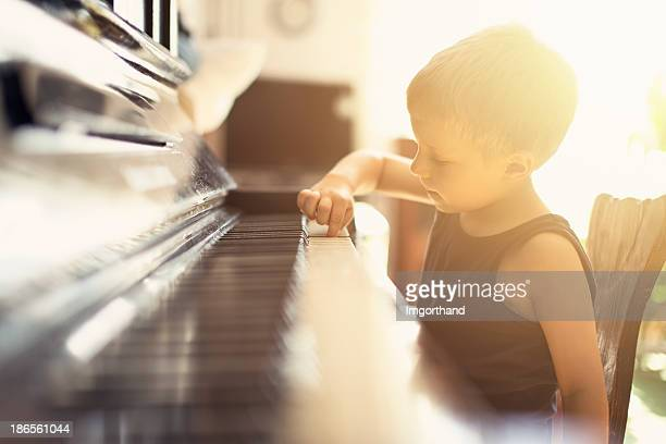 Little boy playing on grandmother piano