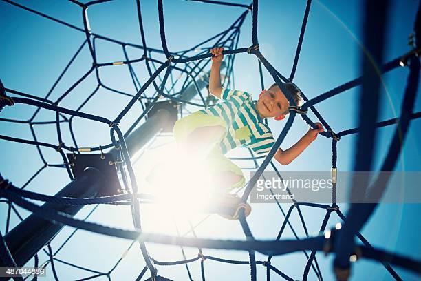 Kleiner Junge spielt auf Spielplatz Klettern-Webstreifen