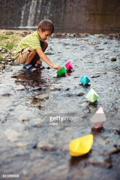 Little boy playing paper boats in stream