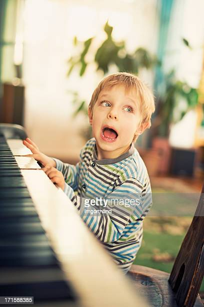 Little boy playing piano and singing.