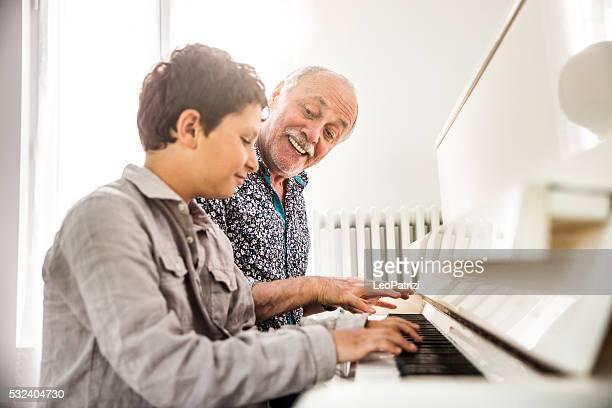 Petit garçon jouant piano avec son grand-père