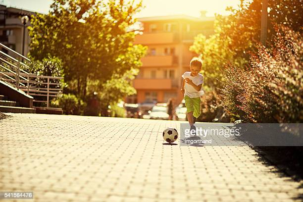 Little boy playing soccer on the street