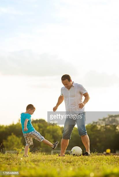 Petit garçon jouant au Soccer avec le père en plein air.