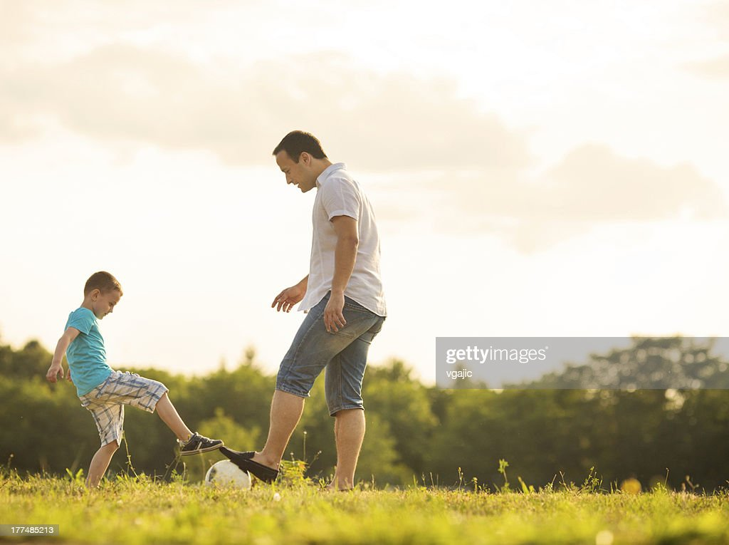 Little Boy Playing Soccer With Father Outdoors. : Stock Photo