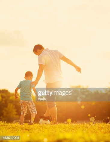 Little Boy Playing Soccer With Father Outdoors.