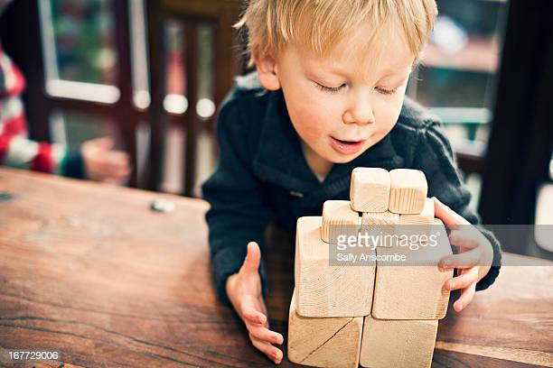 Little boy playing stacking wooden blocks