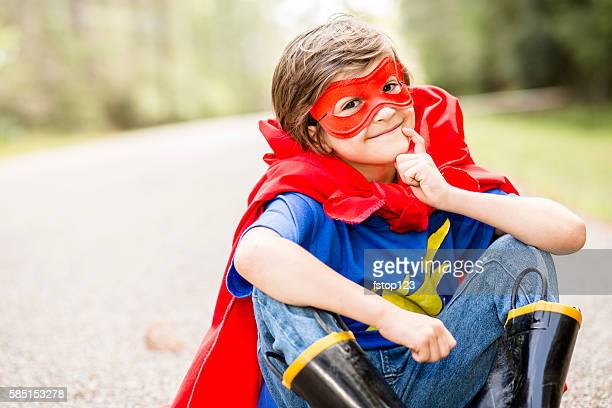 Little boy playing superhero outdoors.