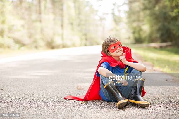 Little boy playing superhero outdoors. Pretend, dress up.