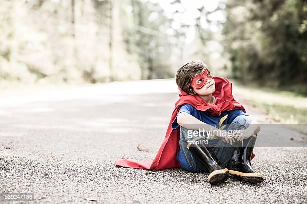 Little boy playing superhero outdoors. Pretend, dress up.