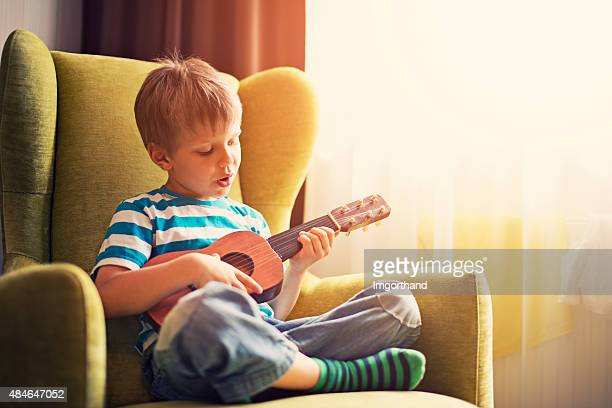 Little boy playing the guitar and singing
