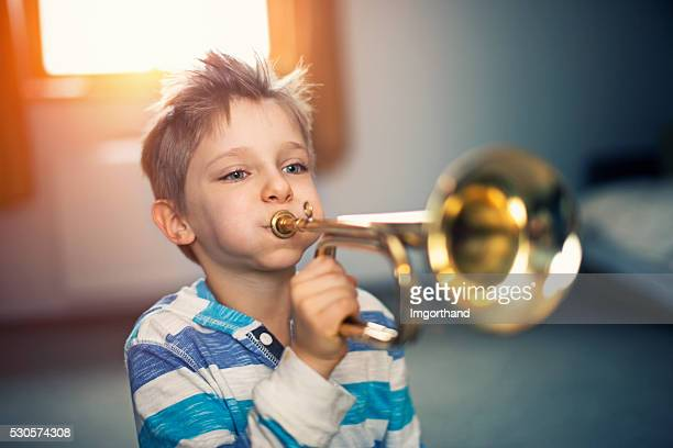 Little boy playing trumpet at home