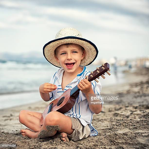 Little boy playing ukulele on the beach.
