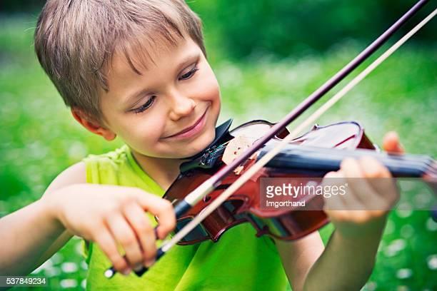 Little boy playing violin on grass field