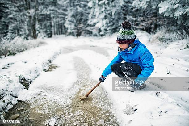 Little boy playing with a frozen puddle in winter forest