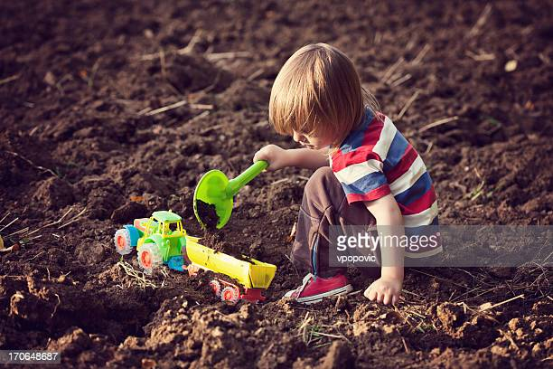 Little boy playing with a toy tractor