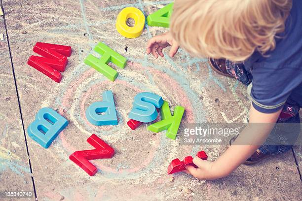 Little boy playing with alphabet letters