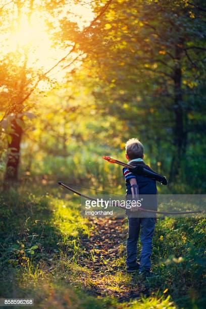 Little boy playing with bow in forest