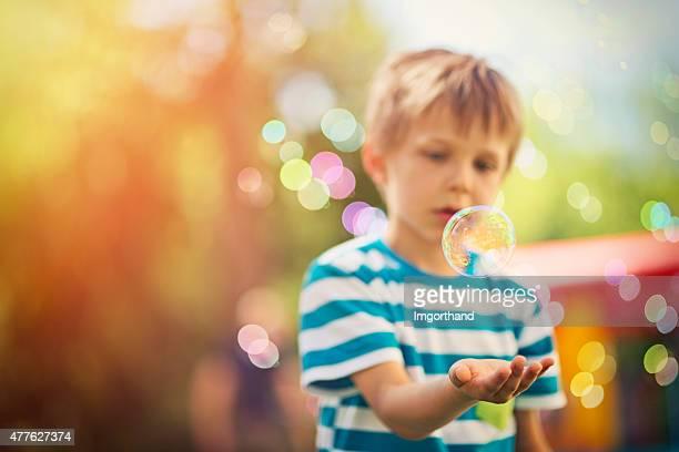 Kleiner Junge spielt mit Blasen im Freien kids party