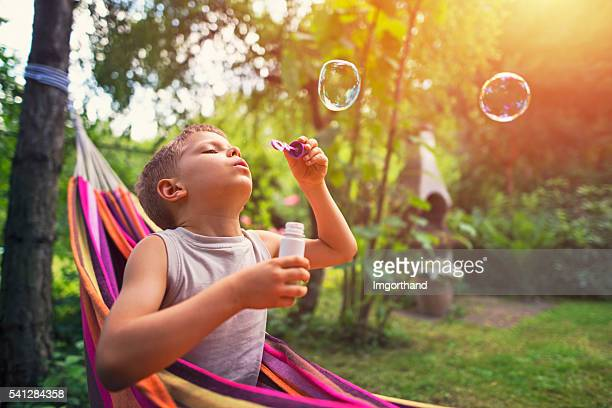 Little boy playing with bubbles on hammock